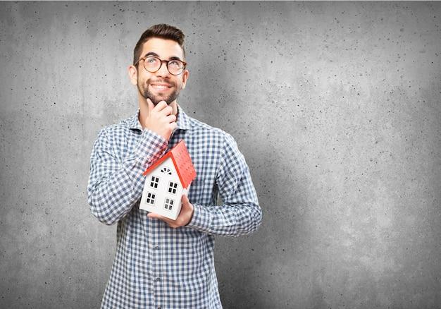 Homem pensativo que prende uma casa em miniatura