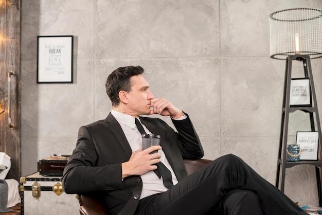 Homem pensativo, segurando a xícara de café no quarto