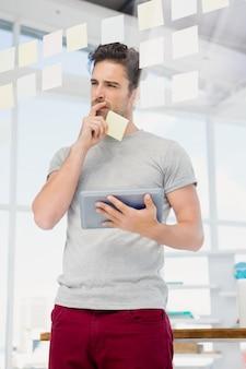 Homem pensativo, segurando o tablet digital e notas autoadesivas