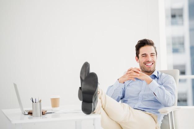 Homem pensativo, sentado com os pés na mesa