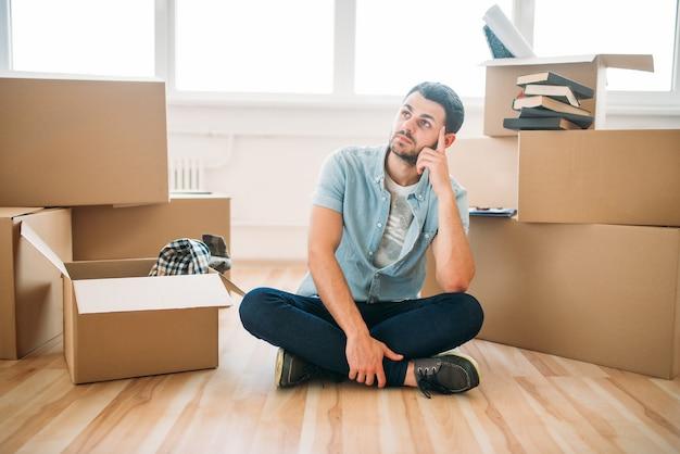Homem pensativo sentado em pose de ioga entre caixas de papelão, inauguração de casa. mudança para nova casa