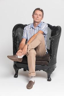 Homem pensativo sentado em uma poltrona cinza e segurando isolado no fundo branco