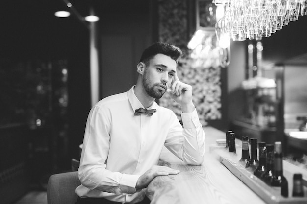 Homem pensativo sentado no balcão de bar