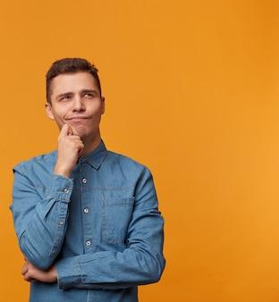 Homem pensativo, sonhador e atraente em uma camisa jeans da moda, olhando para a distância, segurando a mão perto do queixo, isolada contra uma parede amarela.