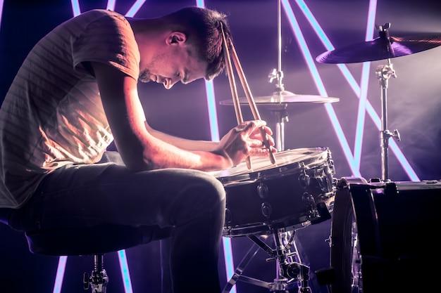 Homem pensativo, tocando bateria.