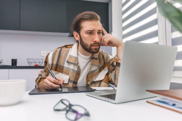 Homem pensativo trabalhando em uma mesa digitalizadora e olhando para um laptop