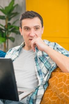 Homem pensativo, trabalhando no laptop e desviar o olhar