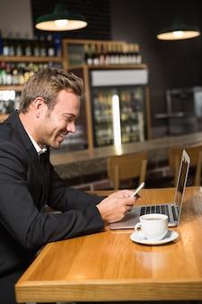 Homem pensativo usando laptop e smartphone