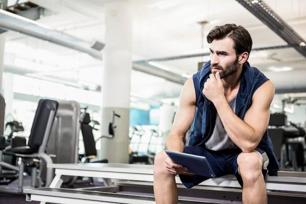 Homem pensativo usando tablet no ginásio