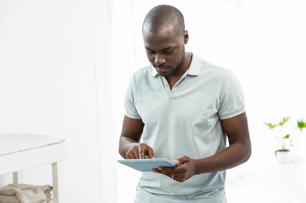 Homem pensativo usando um tablet digital em casa