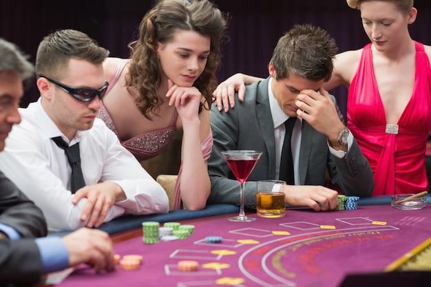 Homem perdido na mesa de poker com mulher reconfortante