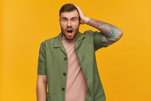 Homem perplexo, cara chocado com cabelo e barba morenos. jaqueta verde de mangas curtas. tem tatuagem. tocando sua cabeça. esqueci algo. isolado sobre a parede amarela