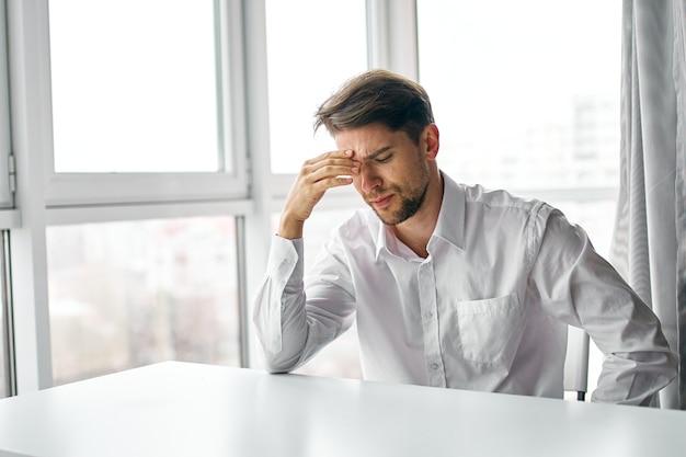 Homem perplexo sentado à mesa, escritório, trabalho, negócios, finanças
