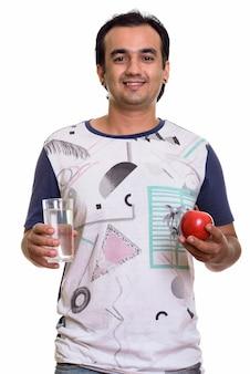 Homem persa feliz segurando uma maçã vermelha e um copo d'água