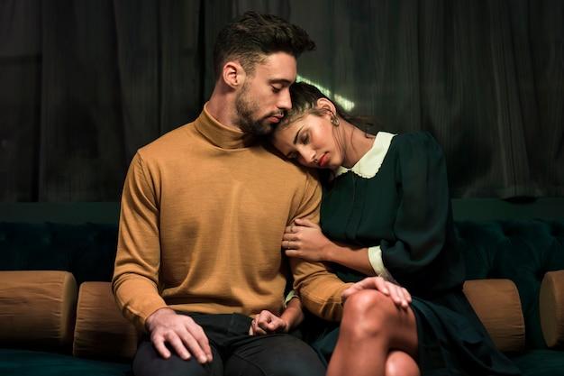 Homem perto de mulher deitada no ombro no sofá