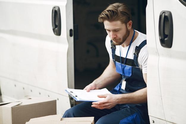 Homem perto do caminhão. cara com um uniforme de entrega. homem com área de transferência.