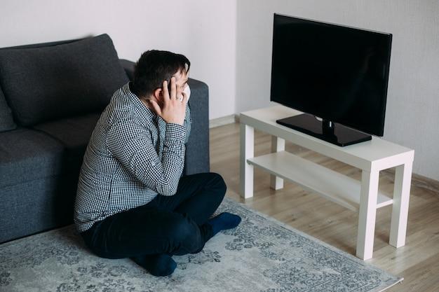 Homem perturbado espantado na máscara assistindo tv news