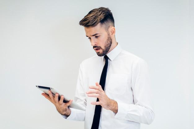 Homem perturbado olhando para um tablet