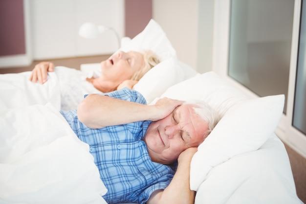 Homem perturbado porque sua esposa está roncando