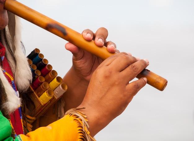 Homem peruano em traje nativo tocando flauta