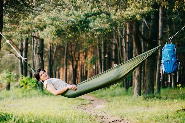Homem peruano novo feliz do redskin que descansa e que relaxa na rede exterior na natureza na floresta no dia ensolarado do verão com pinheiros e grama verde. viagens, férias, turismo, férias. sonhando no parque.
