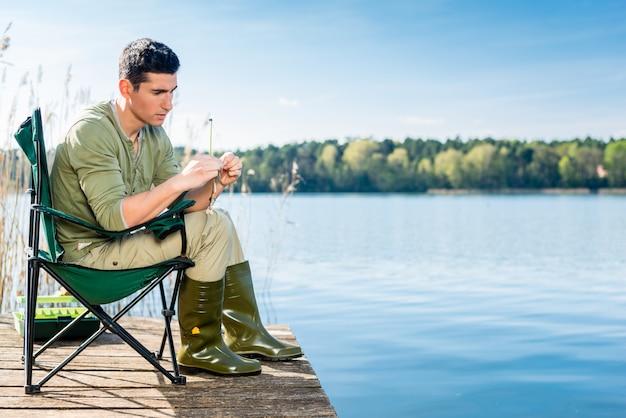 Homem pesca no lago fixação isca na vara de pesca