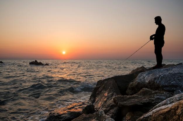 Homem pesca, pôr do sol