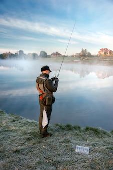 Homem pescando em um lago ao pôr do sol. vista traseira.