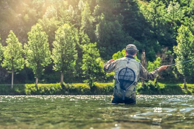 Homem pescando truta e salmão nos rios dos pirenéus catalães com todo o equipamento de pesca esportiva