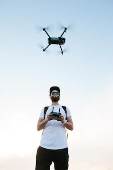 Homem pilotando um helicóptero drone operando-o