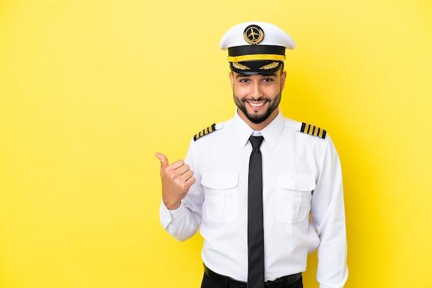 Homem piloto árabe de avião isolado em fundo amarelo apontando para o lado para apresentar um produto