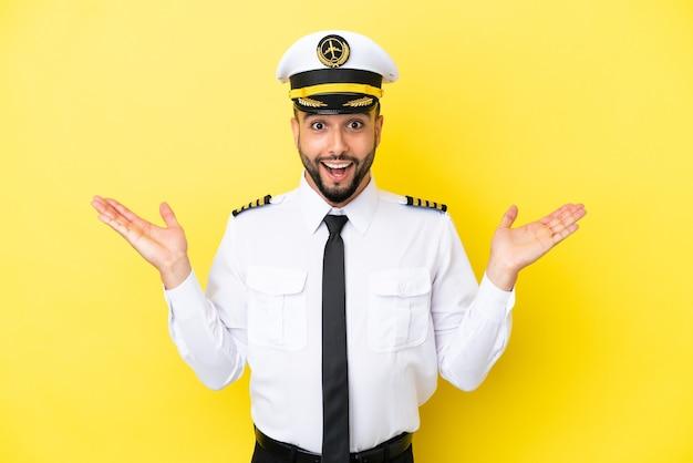 Homem piloto árabe de avião isolado em fundo amarelo com expressão facial chocada