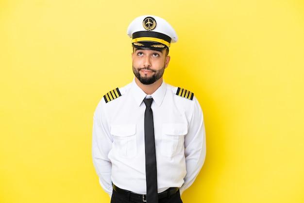 Homem piloto árabe de avião isolado em fundo amarelo e olhando para cima