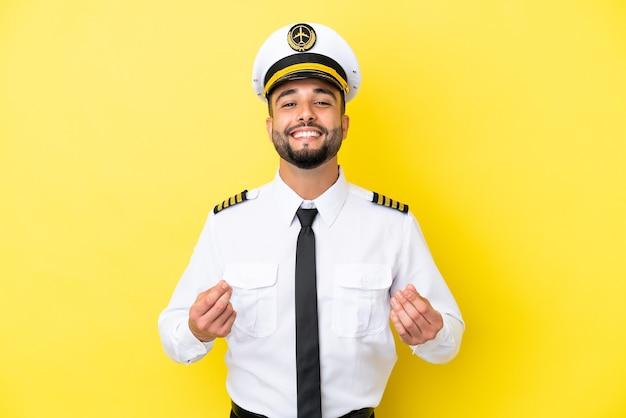 Homem piloto árabe de avião isolado em fundo amarelo fazendo gesto de dinheiro
