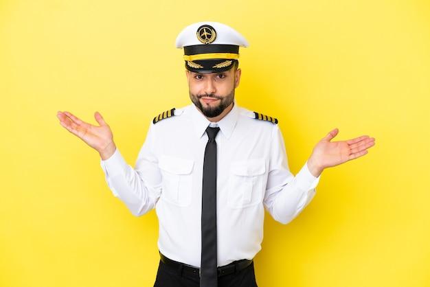 Homem piloto árabe de avião isolado em fundo amarelo, tendo dúvidas ao levantar as mãos