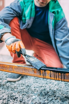 Homem pinta um poste de metal com um pincel, close-up