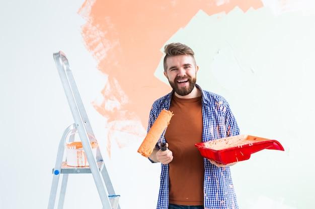 Homem pintando a parede em seu novo apartamento. conceito de renovação e redecoração.