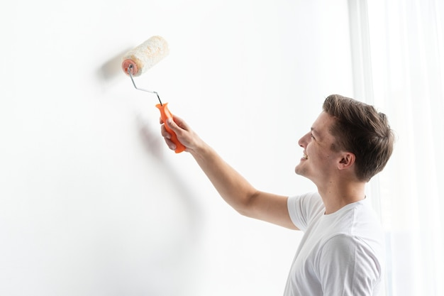 Homem pintando sua parede de branco