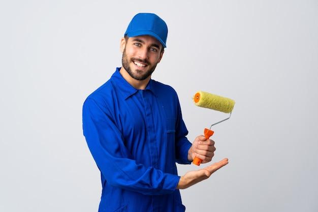 Homem pintor segurando um rolo de pintura, apresentando uma ideia enquanto olha sorrindo para