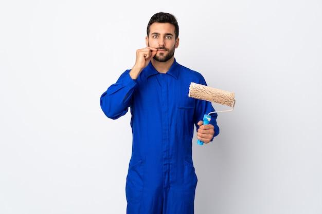 Homem pintor segurando um rolo de pintura isolado na parede branca, mostrando um sinal de gesto de silêncio