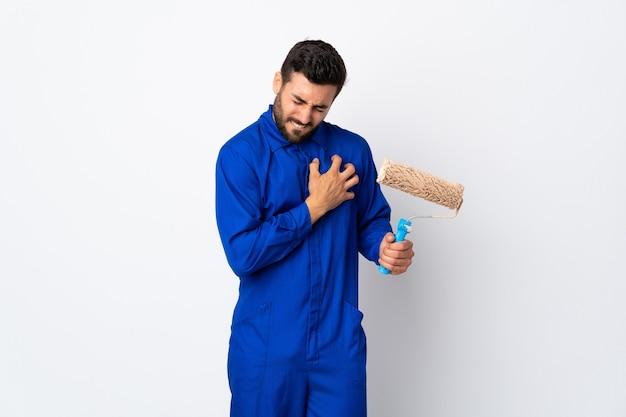 Homem pintor segurando um rolo de pintura isolado no fundo branco, sentindo uma dor no coração