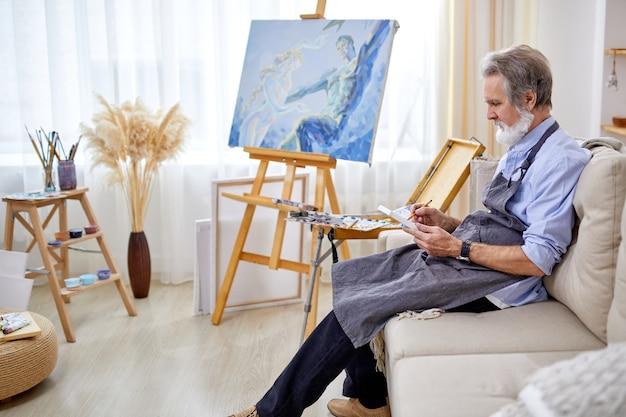 Homem pintor sentado no sofá, concentrado no trabalho com o lápis, sentado olhando para o lençol, no estúdio de arte leve