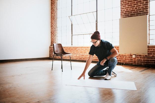 Homem planejando um projeto em um piso de madeira