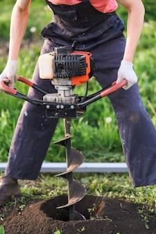 Homem planta uma árvore, mãos com pá cava o solo, natureza, conceito ecológico