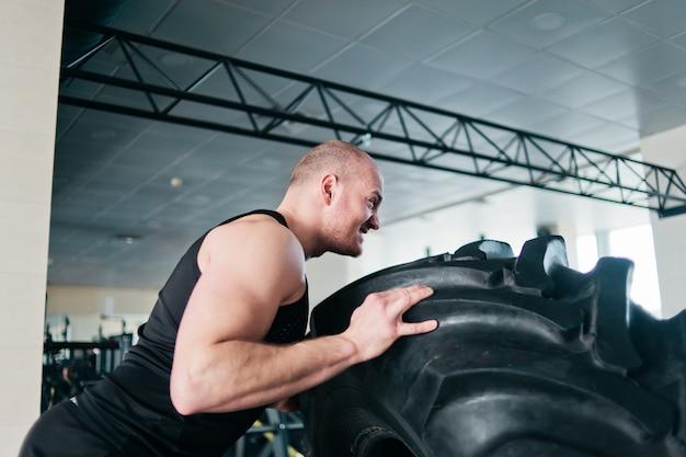 Homem poderoso está empurrando uma grande roda de borracha pesada. treino funcional