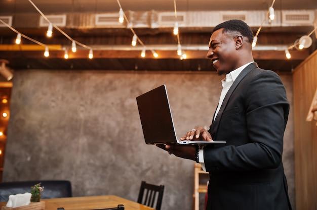 Homem poderoso forte em terno preto de pé e trabalhando com o laptop
