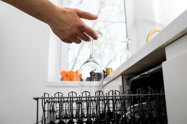 Homem põe pratos na máquina de lavar louça