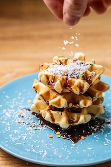 Homem polvilha waffles caseiros de coco