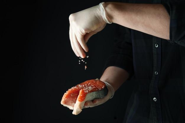 Homem polvilhe sal na carne de salmão na superfície escura