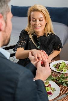 Homem, pôr, anel, ligado, dedo mulher, em, tabela, com, pratos